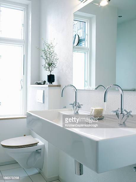 Washbasin with two faucets next to toilet
