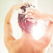 Mid adult woman washing a hair at domestic bathroom