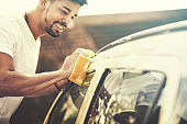 Young handsome man is washing car outdoor.