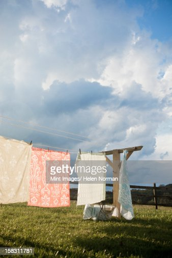 A washing line with household linens and washing hung out to dry in the fresh air. : Stock Photo