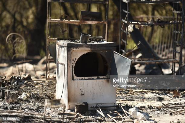 A washing machine is seen at a burned out residential property after the Wall fire tore through the area and burned dozens of homes and structures in...