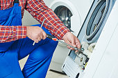 Washing machine repair. Repairer hands with screwdriver disassembling damaged unit for repair