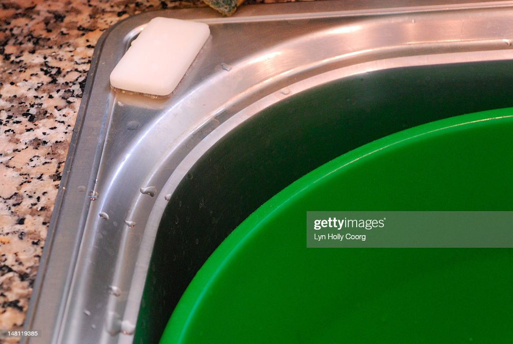 Washing up bowl, a bar of soap and a sink : Stock Photo