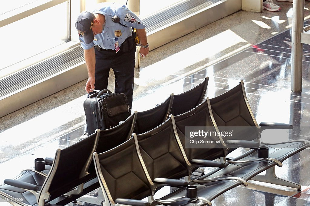 A Washington Area Airports Authority Police officer inspects an unattended suitcase at Ronald Reagan National Airport May 27, 2016 in Arlington, VA. The bag was later claimed by its owner and the officer confirmed ownership with identification. According to AAA, 'more than 38 million Americans will travel this Memorial Day weekend. That is the second-highest Memorial Day travel volume on record and the most since 2005. Spurred by the lowest gas prices in more than a decade, about 700,000 more people will travel compared to last year.'