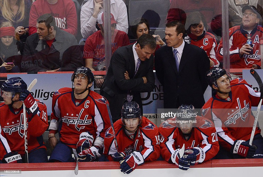Washington Capitals assistant coach Tim Hunter, center left, talks with Washington Capitals head coach Adam Oates during the third period of the game at the Verizon Center on Sunday, January 27, 2013. The Washington Capitals defeated the Buffalo Sabres 3-2 for their first win of the season.