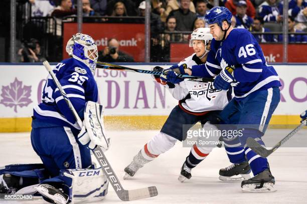 Washington Capitals Center Jay Beagle and Toronto Maple Leafs Defenceman Roman Polak fight for the puck in front of Toronto Maple Leafs Goalie Curtis...