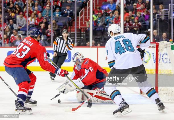 Washington Capitals center Jay Beagle covers goalie Philipp Grubauer as San Jose Sharks center Tomas Hertl moves in during a NHL game between the...