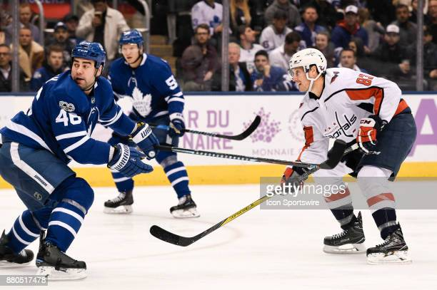 Washington Capitals Center Jay Beagle shoots the puck past Toronto Maple Leafs Defenceman Roman Polak during the NHL regular season hockey game...