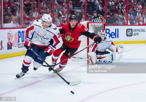 Washington Capitals Center Lars Eller stickhandles the puck against Ottawa Senators Center JeanGabriel Pageau during the NHL game between the Ottawa...
