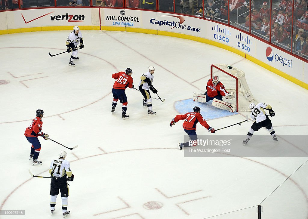Washington Capitals defenseman Karl Alzner (27), center right, gets a stick on the puck as he tries to block the power play shot by Pittsburgh Penguins left wing James Neal (18) during the third period of the game at the Verizon Center on Sunday, February 3, 2013. The Pittsburgh Penguins defeated the Washington Capitals 6-3.