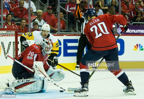 Washington Capitals goalie Braden Holtby covers the puck as Pittsburgh Penguins center Greg McKegg skates in during a NHL game between the Washington...