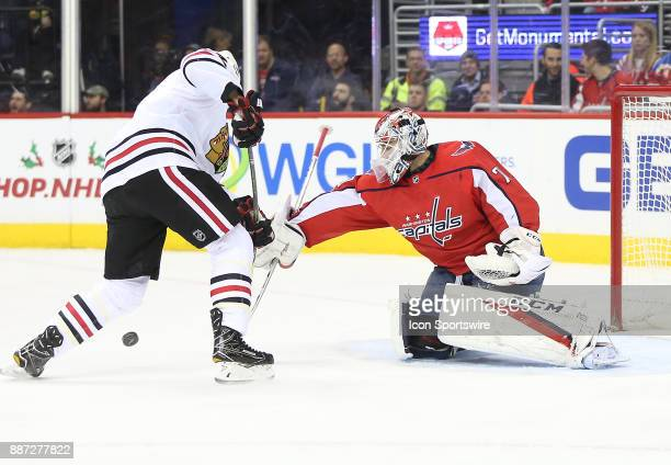 Washington Capitals goalie Braden Holtby poke the puck away from Chicago Blackhawks left wing Lance Bouma in the first period during a NHL game...