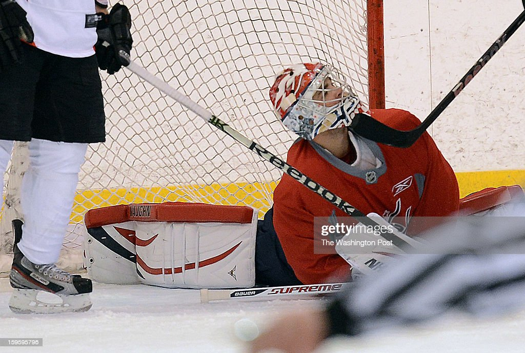 Washington Capitals goalie Michal Neuvirth (30) gets an accidental stick under his face mask during a scrimmage against the team's ECHL farm affiliate-the Reading Royals- at the Kettler IcePlex on Tuesday, January 15, 1013.