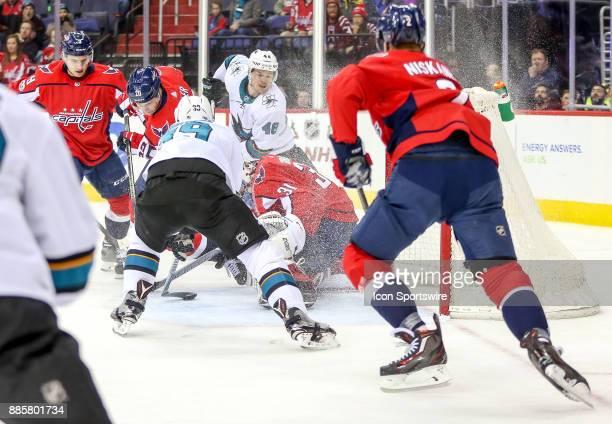 Washington Capitals goalie Philipp Grubauer pounces on the puck on the stick of San Jose Sharks center Logan Couture during a NHL game between the...