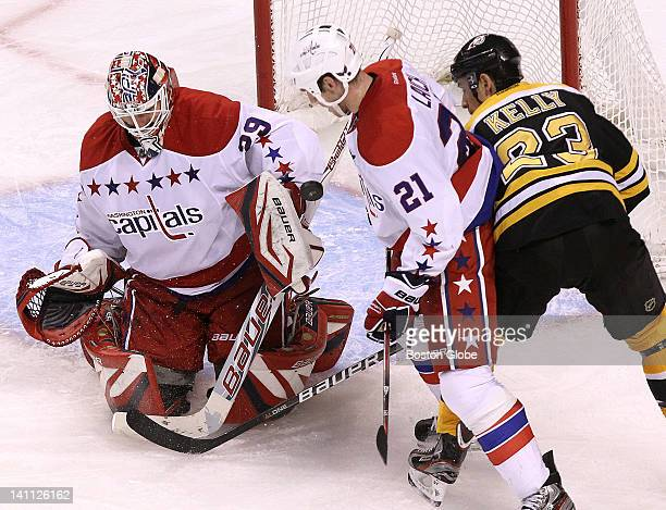 Washington Capitals goalie Tomas Vokoun makes a save during the third period as Boston Bruins center Chris Kelly looks for the rebound Boston Bruins...