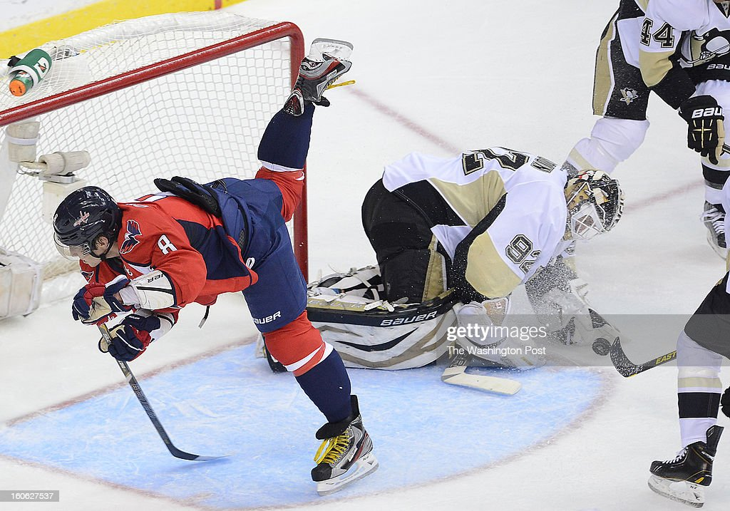 Washington Capitals left wing Alex Ovechkin (8) goes flying across the face of the goal after Pittsburgh Penguins goalie Tomas Vokoun (92) tripped him up while making the save during the third period of the game at the Verizon Center on Sunday, February 3, 2013. The Pittsburgh Penguins defeated the Washington Capitals 6-3.