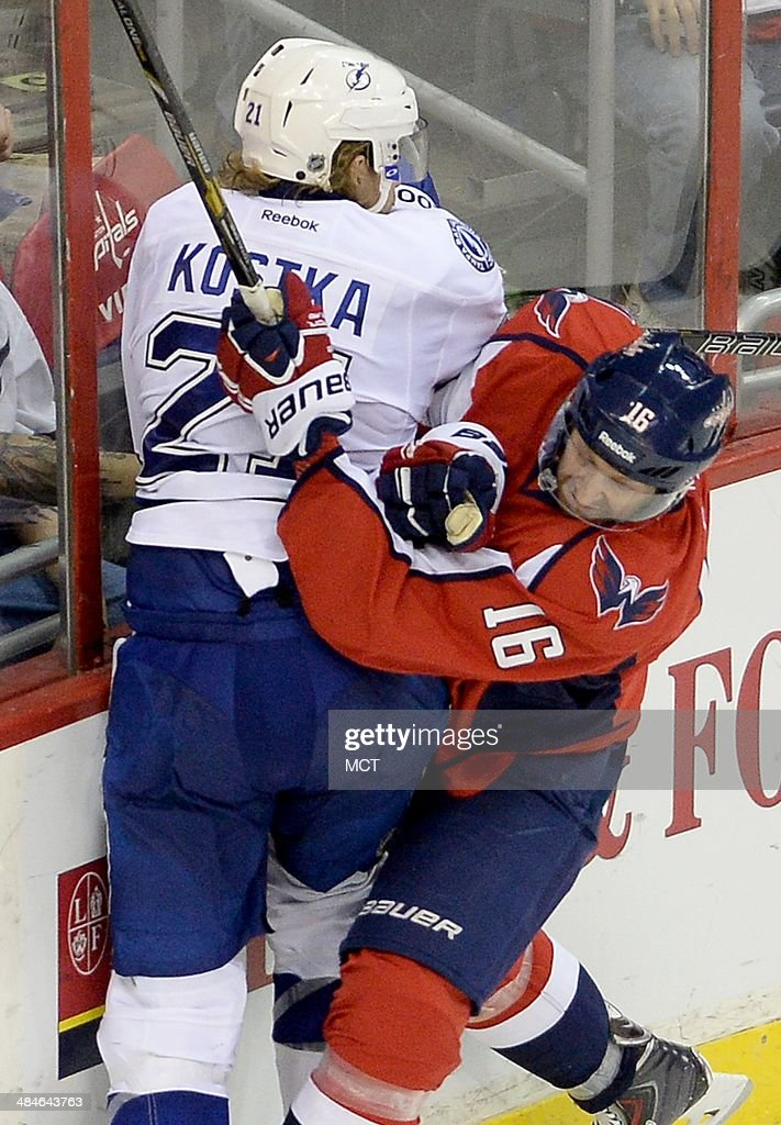 Washington Capitals right wing Eric Fehr (16) checks Tampa Bay Lightning defenseman Mike Kostka (21) in the third period at the Verizon Center in Washington, Sunday, April 13, 2014. The Lightning defeated the Capitals in a shootout, 1-0.