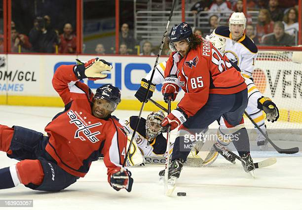 Washington Capitals right wing Joel Ward hits the ice as Capitals center Mathieu Perreault reaches back for the puck in the second period against the...