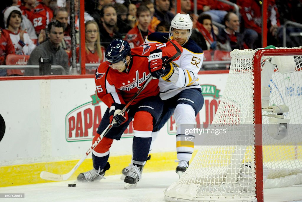 Washington Capitals right wing Joey Crabb (15) fights for a loose puck with Buffalo Sabres defenseman Alexander Sulzer (52) during first-period action at the Verizon Center in Washington, D.C., Sunday, January 27, 2013.