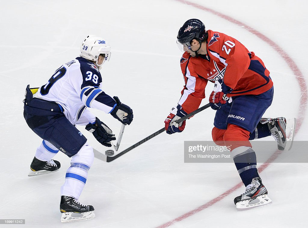 Washington Capitals right wing Troy Brouwer (20), right, gets the puck past Winnipeg Jets defenseman Tobias Enstrom (39) during the third period of the game at Verizon Center on Tuesday, January 22, 2013. The Washington Capitals lost 4-2 to the Winnipeg Jets in the Washington Capitals' season home opener.