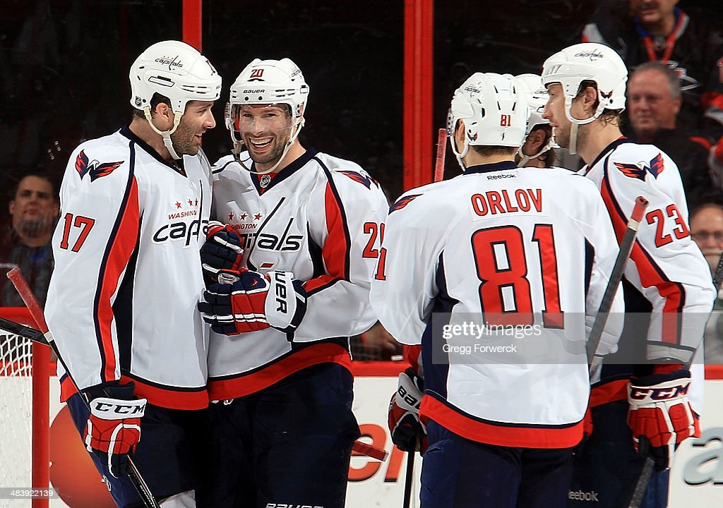Washington Capitals teammates surround Troy Brouwer #20 following his second goal against the Carolina Hurricanes in the third period of their NHL game at PNC Arena on April 10, 2014 in Raleigh, North Carolina.