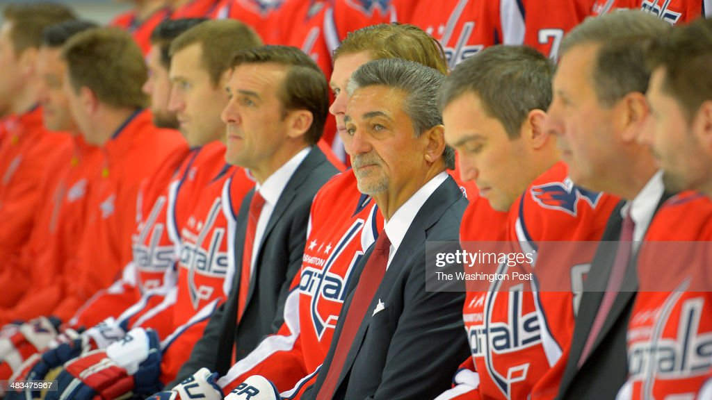 Washington Capitgals' General Manager George McPhee , left, and owner Ted Leonsis, center, sit with their team at the annual Washington Capitals team photo shoot at the Kettler Capitals Iceplex in Arlington VA, March 27, 2014.