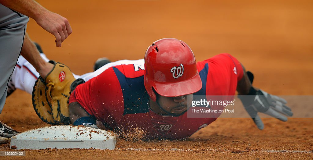 Washington center fielder Denard Span (2) dives back into first base on a pick off attempt as the Florida Marlins tie the Washington Nationals 2 -2 in 10 innings during Grapefruit League baseball in Viera FL, February 24, 2012 .