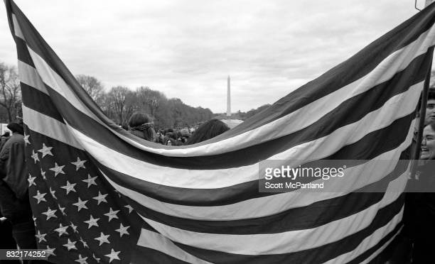 An American Flag is held up in front of the camera by AntiVietnam activists in Washington DC The Washington Monument and hundreds of other protesters...