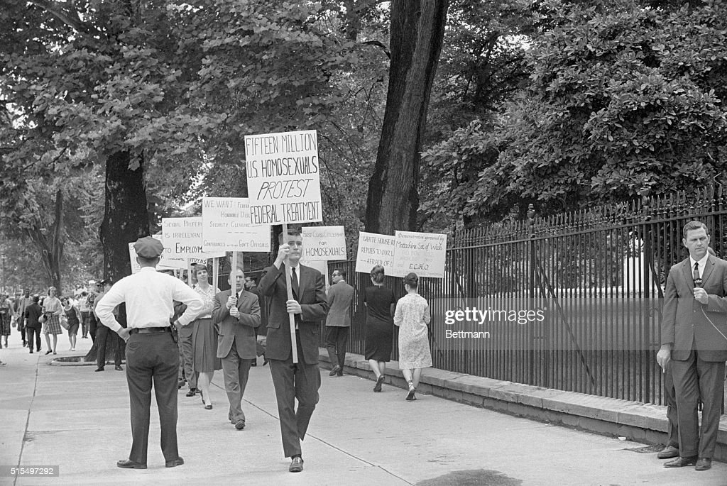 Homosexuals Picket A couple of G I's and their girlfriends pass by as a group of 'homosexual American citizens' picket outside the White house on...