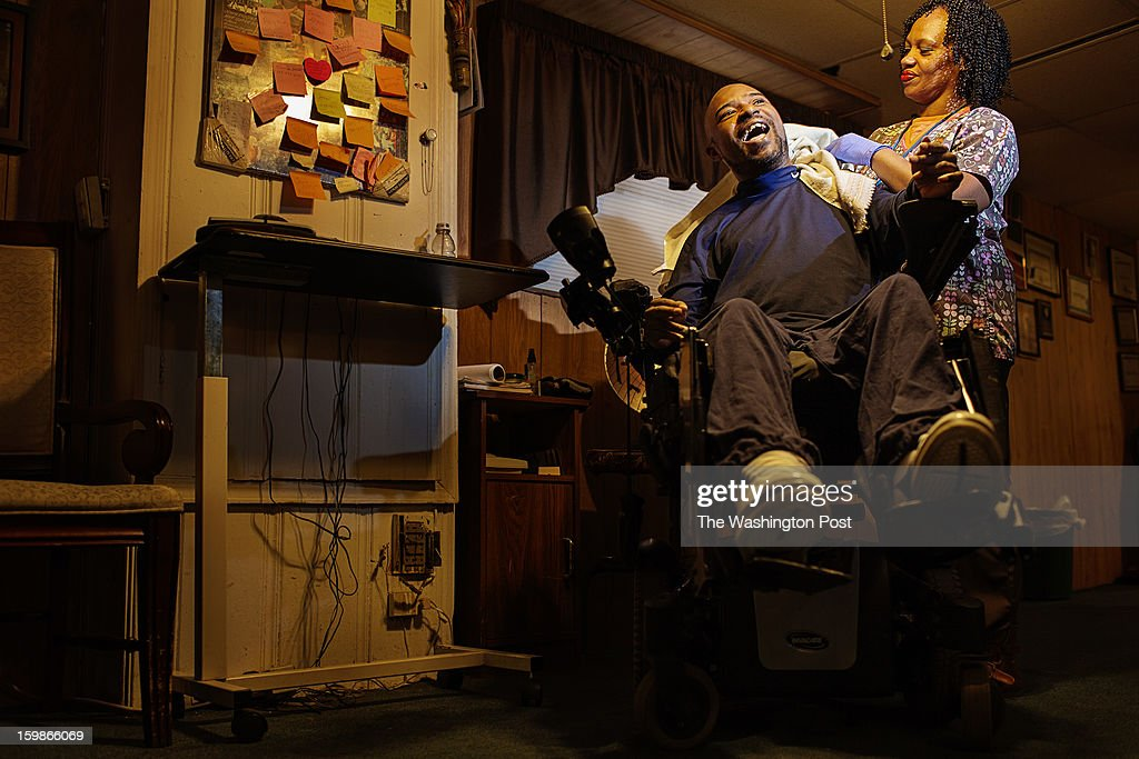 Washington, DC - January 21, 2013- Robert 'Bobby' Coward, 48, (left) bed) is all smiles after receiving a shave from his home health care aid, Lois Wilson, (right) at his at his home in Washington, DC on Monday January 21, 2013. A car accident in 1991 left Coward paralyzed.