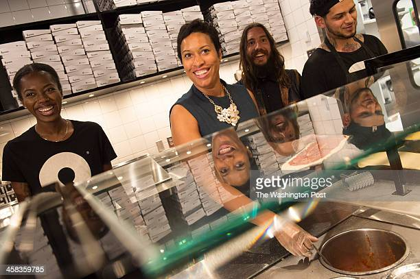 Washington DC Mayor Muriel Bowser flanked by Kyonna Hicks left and Pizza owner Mike Lastoria at right tries her hand at pizza making at Pizza after...