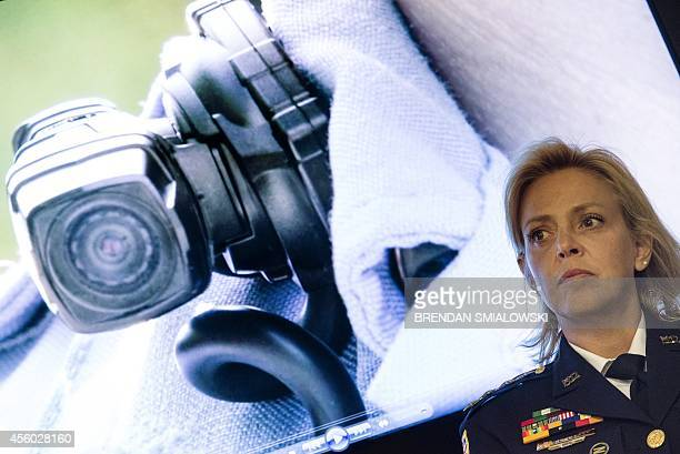 Washington DC Police Chief Cathy Lanier is seen near an image of a collar mounted body camera while waiting to speak during a press conference at...