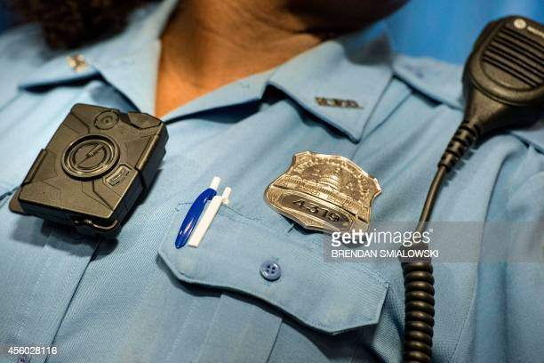 Washington DC Police Officer Debra Domino models a body camera before a press conference at City Hall September 24 2014 in Washington DC The...