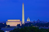 A skyline view of Washington, District of Columbia at dusk. The Lincoln Memorial, Washington Monument and the U.S. Capitol Building illuminate the Washington, D.C. skyline as seen from the nearby Iwo