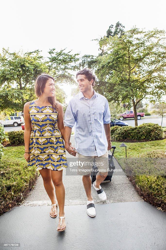 USA, Washington, Everett, Couple walking, man pulling suitcase : Stock Photo