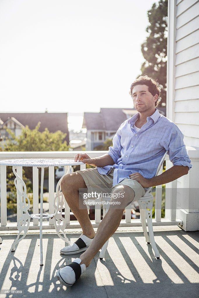 USA, Washington, Everett, Portrait of young man relaxing on balcony