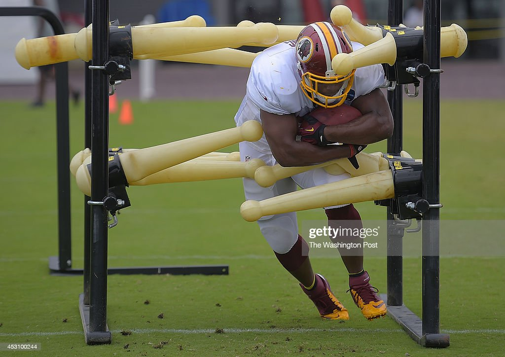 Washington fullback Darrel Young breaks through a set of obstacles during fan appreciation day on day 10 of the Washington Redskins training camp in Richmond VA, August 2, 2014.