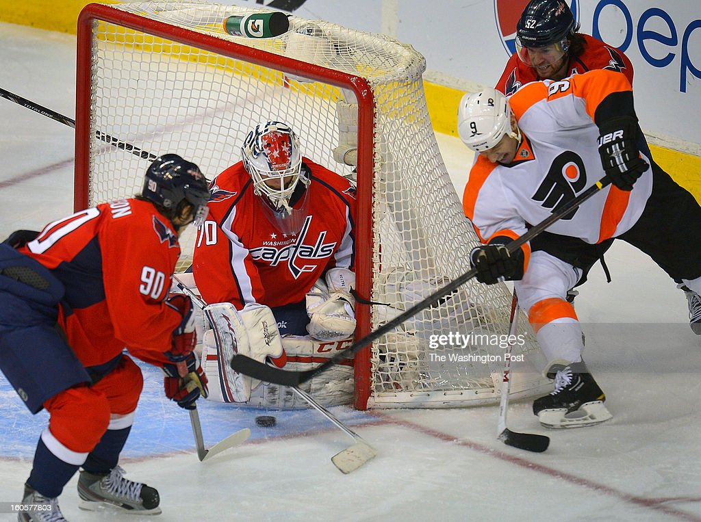 Washington goalie Braden Holtby (70), center, stops a around the net shot by former Capital, Philadelphia right wing Mike Knuble (9), center right, with Mike Green riding his back as the Washington Capitals defeat the Philadelphia Flyers 3 - 2 at the Verizon Center in Washington DC, February 1, 2012 .