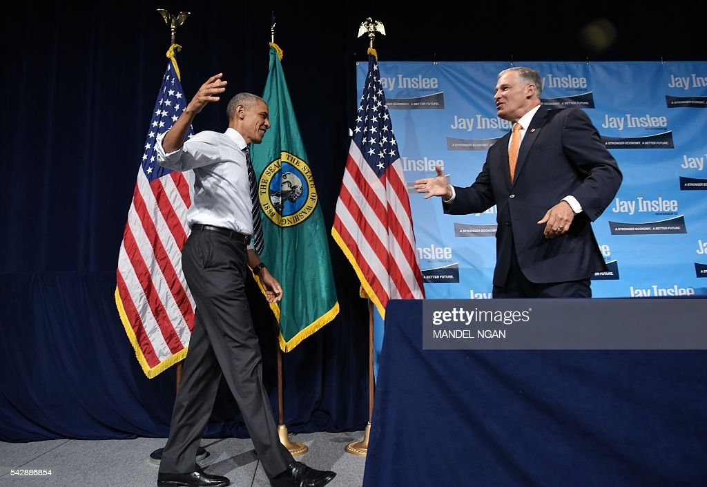 Washington Governor Jay Inslee (R) greets US President Barack Obama after introducing him at a fundraiser at the Washington State Convention Center in Seattle, Washington on June 24, 2016. / AFP / MANDEL