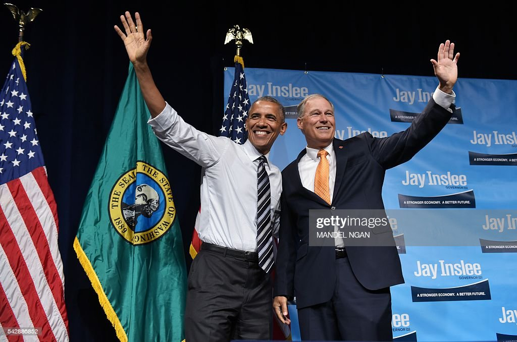 Washington Governor Jay Inslee waves with US President Barack Obama after introducing him at a fundraiser at the Washington State Convention Center in Seattle, Washington on June 24, 2016. / AFP / MANDEL