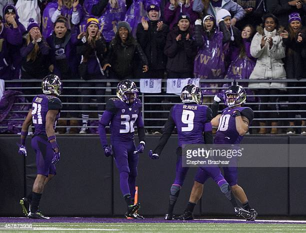 Washington Huskies linebacker John Timu celebrates returning an interception for a touchdown with teammates defensive back Brandon Beaver defensive...