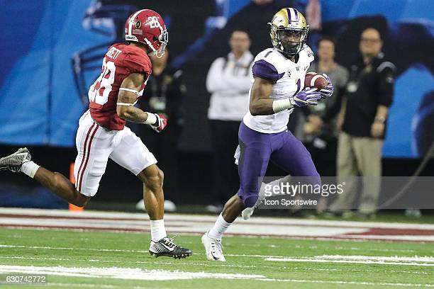 Washington Huskies wide receiver John Ross returns a punt chased by Alabama Crimson Tide defensive back Anthony Averett during the second half of the...