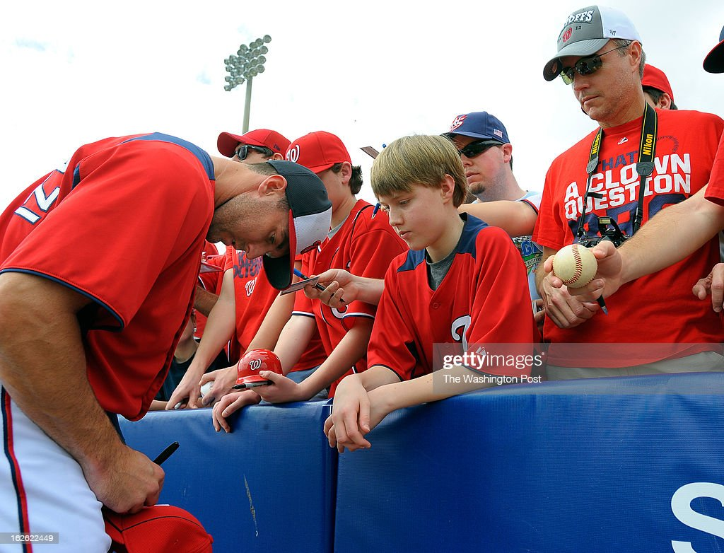 Washington infielder Stephen Lombardozzi (1), left signs autographs for Will Sullivan, center, of Alexandria Va as his father Bill Sullivan looks on before the Florida Marlins play the Washington Nationals in Grapefruit League baseball in Viera FL, February 24, 2012 .