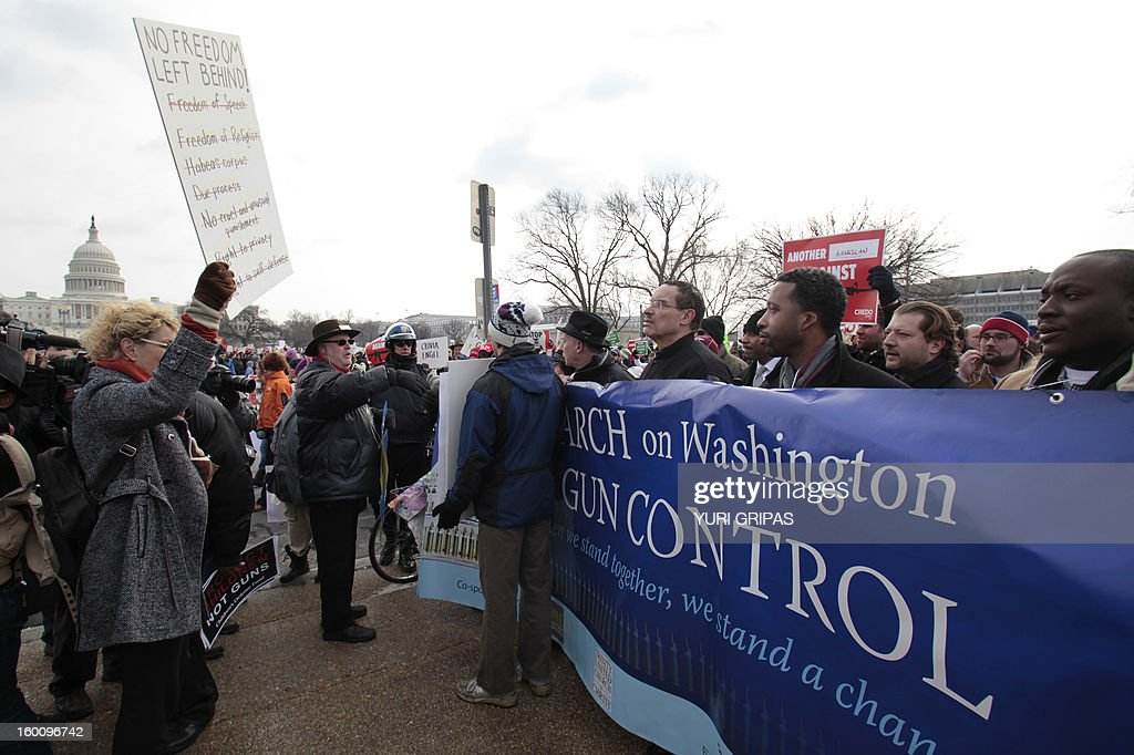 Washington Mayor Vincent Gray (3rd R) looks on at a pro-gun activist protesting against the March on Washington for Gun Control on January 26, 2013 in Washington. Thousands of people participated in the march in response to last month's school shooting in Newtown, Connecticut.