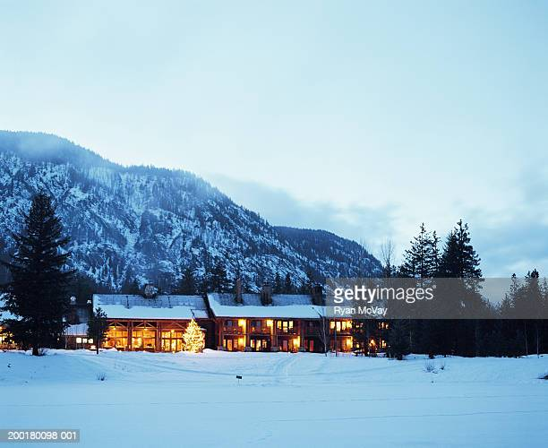 USA, Washington, Mazama, illuminated lodge beside frozen lake, dusk