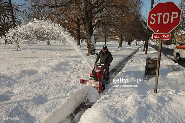 Washington Metropolitan Area Transit Authority employee Gene Walker uses a snowblower to clear a sidewalk near the BrooklandCUA stop after Winter...