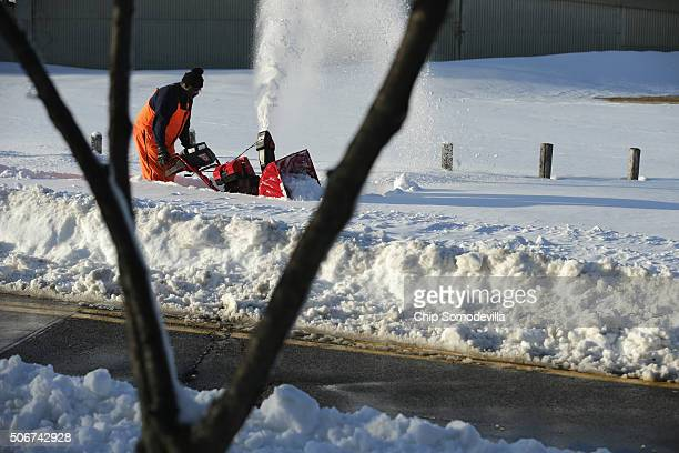 Washington Metropolitan Area Transit Authority employee uses a snowblower while trying to find and clear a sidewalk near the BrooklandCUA stop after...