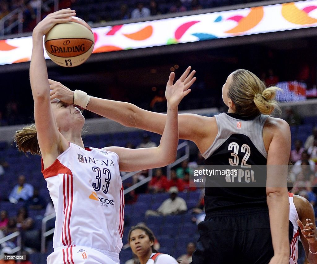 Washington Mystics center Emma Meesseman (33) pulls down a rebound and catches a hand to her face from San Antonio Silver Stars center Jayne Appel (32) in the third quarter at the Verizon Center in Washington, D.C., Tuesday, July 16, 2013, The Mystics defeated the Silver Stars, 86-64.