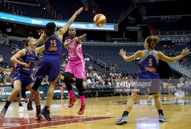 Washington Mystics guard Allison Hightower throws a long pass between Phoenix Mercury forward Monique Currie and guard Leilani Mitchell during a WNBA...