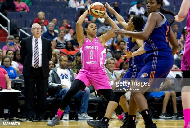 Washington Mystics guard Natasha Cloud holds the ball away from Phoenix Mercury forward Monique Currie during a WNBA game on August 18 between the...